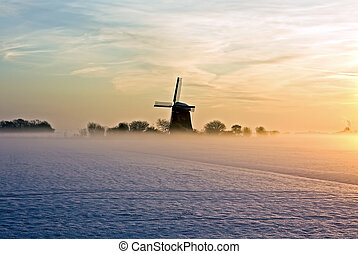 Traditional windmill at twilight with fog and snow in winter in the Netherlands