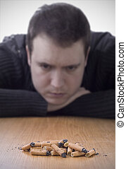 quitting smoking, pile of cigarette butts on table with man...