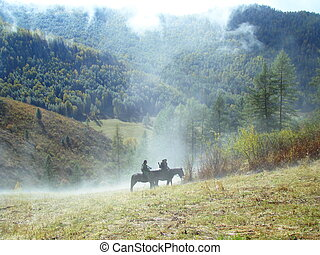 Two hunters go on horses in a valley of mountains