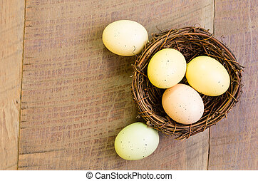 Birds nest with eggs on wooden table