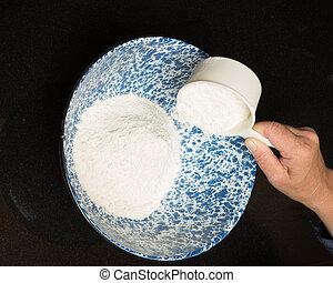 Baker measuring flour into bowl