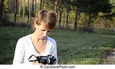 Young woman photographer in autumn park