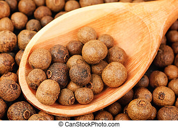 Background texture of whole allspice(jamaica pepper) with wooden spoon Used as a spice in cuisines all over the world. Also used in medicine.