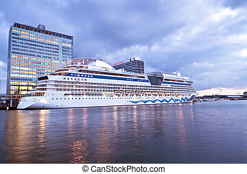 Cruise boat in Amsterdam harbor in the Netherlands at...