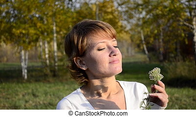 Young woman smelling flowers in the autumn park