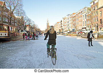 Biking on frozen canals in Amsterdam the Netherlands