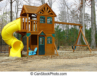A childs playset swing and slide outside on a cloudy winter...