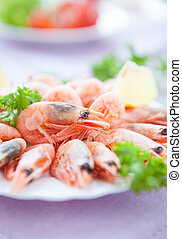 Many great shrimp on white plate with greens, close up