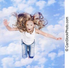 Photo of little girl jumping over the blue sky with clouds