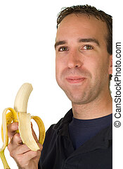 Banana Man - A man chewing a fresh banana, isolated on a...