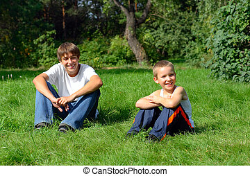 Brothers In The Park - Happy Brothers sit on the grass in...
