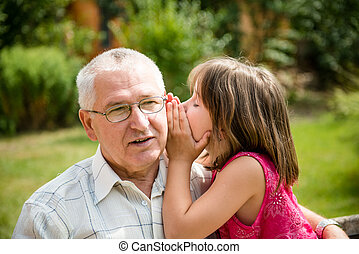 Tell me secret - Little girl whispering her grandfather a...