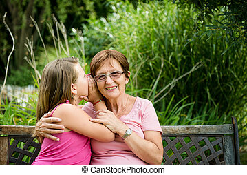 I tell you secret - Little girl whispering her grandmother a...