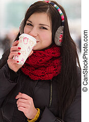 Gril drinking coffee in iwinter - Teenager girl drinks hot...