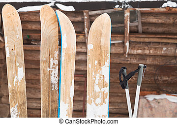 two pairs of wide skis and log house wall in winter day