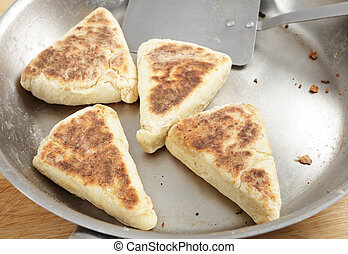 Scottish girdle scones cooking - Scottish girdle scones on a...