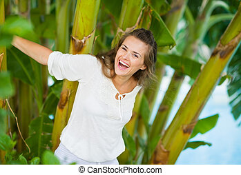 Happy young woman among tropical palms