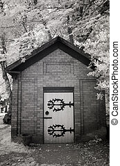 Infrared Photo of a Small Brick Building at a Cemetery -...