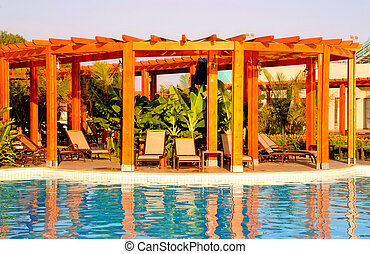 resort swimming pool, wood pergola and deck chairs - summer...