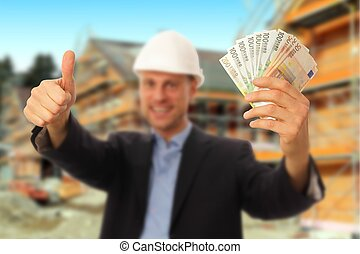 Architect with money and thumb up in front of a construction site