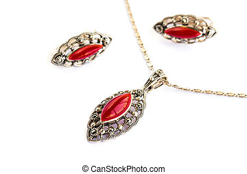 Necklace and earrings wirh red stones isolated on white...