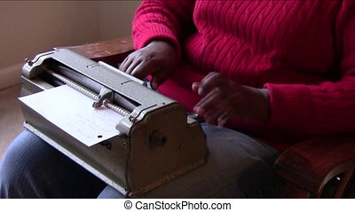 Writing In Braille - Visually impaired woman making braille...