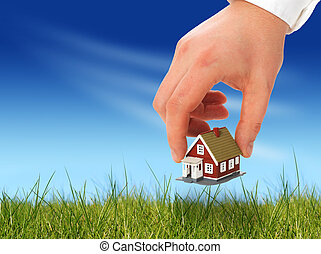 Real estate. - House in the hand over sky background.