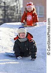 Children slide down icy hill