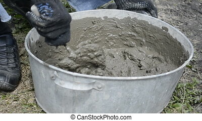 Man knead the concrete in the tub