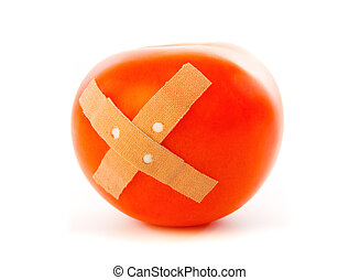 Tomato with plaster against white background