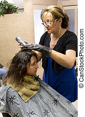Hairdresser with Client - A hairdresser working on a clients...
