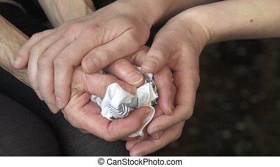 comforting hands - young hands comforting older hands