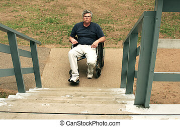 blocked access - man in wheelchair facing a barrier of...