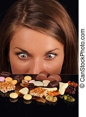 Attractive Woman starring on sweets on a table