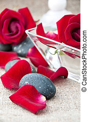 Spa stones and rose petals on a light background