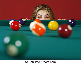 Checking for a shot while playing pool - Photo of a young...