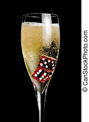 champagne flute with golden bubbles and red dice on black...
