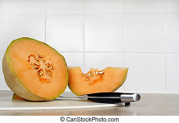 cantaloupe on a cutting board with knife