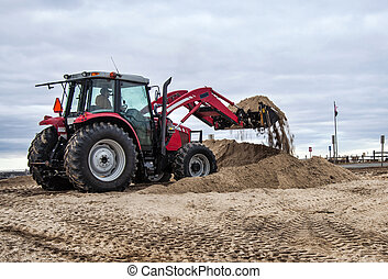 Rebuilding the sand dunes that were washed away during the...