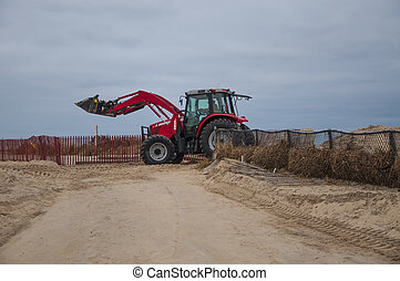Beach Repairs - A payloader carries sand to rebuild the...