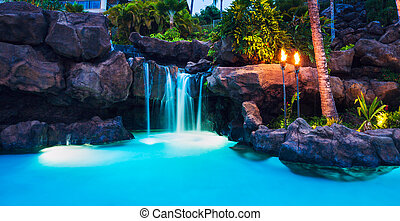 Tropical Resort Pool and Waterfall at Sunset in Hawaii