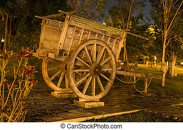 Ancient wooden cart in a park in night illumination