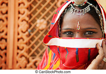 Traditional Indian woman in sari costume covered her face...