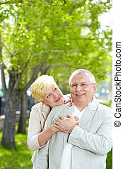 Couple outside - Portrait of happy mature woman hugging her...