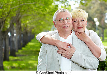Senior couple - Portrait of happy mature woman hugging her...