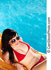 Relaxing - Lovely woman in bikini and sunglasses lying on...