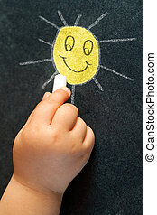Infant hand drawing a smiling sun. - Macro close up of...