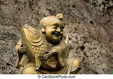 Golden laughing monk with fish - A golden colored statue of...