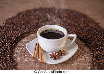 Coffee cup with cinnamon and anise stars over canvas...