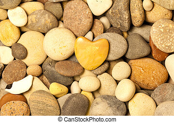 A stone heart shaped surrounded by other natural stones